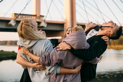 Grupa radosnej młodzieży na tle mostu.