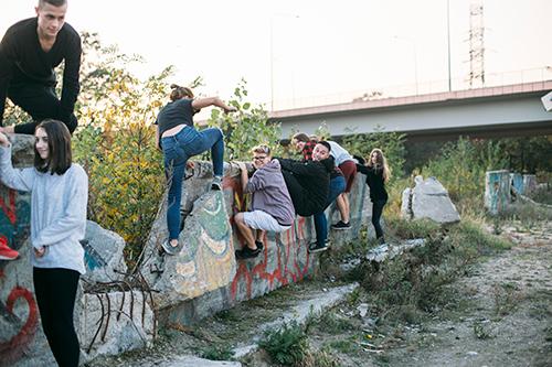 Grupa radosnej młodzieży na tle wiaduktu i resztek betonowego muru z graffiti.